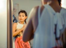 Asiatisches Modell, das herauf Haar im Spiegel bindet Stockfoto