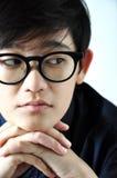 Asiatisches Modell setzte ihre Hände unter Chin und dem Denken Stockfotografie