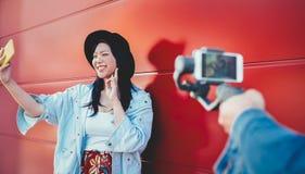 Asiatisches Modemädchen, das den mobilen Smartphone im Freien - glückliche modische Chinesin hat den Spaß herstellt Video vloggin stockfotos
