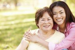Asiatisches Mutter- und Erwachsentochterporträt draußen Stockbild