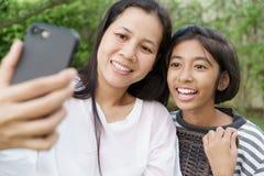 Asiatisches Mutter und Tochter selfie durch Smartphone zusammen im Garten zu Hause Ein Mädchen und Frauen lächeln, wenn sie an Fo stockbilder
