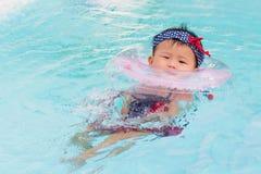 Asiatisches nettes Achtmonatebaby entspannen sich Swimmingpool Stockfotografie
