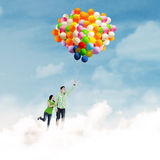 Asiatisches Paarfliegen mit Ballonen Stockfotografie