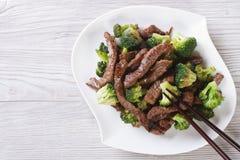 Asiatisches Rindfleisch mit Brokkoli und Essstäbchen horizontale Draufsicht Stockfotos