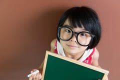Asiatisches Schulkind mit Kreide und Tafel Stockbild