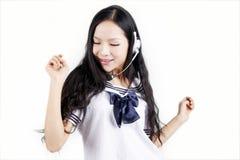 Asiatisches Schulmädchen, das Musik genießt Stockbild