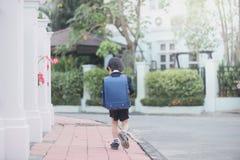 Asiatisches Schulmädchen mit dem rosa Rucksack, der oben schaut Lizenzfreies Stockbild