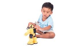 Asiatisches Spiel des kleinen Jungen und kämpfendes Spielzeug des aufgeregten Roboters Lizenzfreie Stockfotos