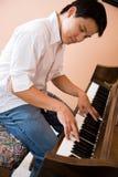 Asiatisches spielendes Klavier Stockfotografie