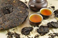 Asiatisches Stillleben des Tees PU-erh mit Dishware und trocknen Blätter Stockbild