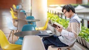 Asiatisches Studentenmann-Lesebuch im Collegegebäude stockfoto