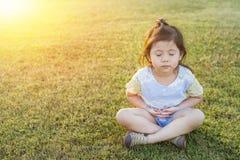 Asiatisches thailändisches kleines nettes Mädchen, das Meditation macht und Yog übt Lizenzfreie Stockfotos
