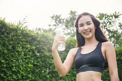 Asiatisches Trinkwasser der jungen Frau nach Sport lizenzfreies stockfoto