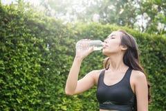 Asiatisches Trinkwasser der jungen Frau nach Sport Stockfotos