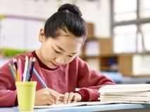 Asiatisches Volksschulemädchen, das im Klassenzimmer studiert Lizenzfreie Stockfotos