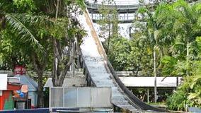 Asiatisches Wasserboot, das hinunter den Schieber mit einem enormen Wasserspritzen bei der Landung im Vergnügungspark in HD läuft stock video footage