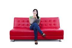 Asiatisches weibliches Denken auf dem roten Sofa - lokalisiert Lizenzfreie Stockfotografie