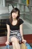 Asiatisches weibliches Käufer-Sitzen stockfoto