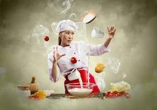 Asiatisches weibliches Kochen mit Magie Lizenzfreie Stockbilder