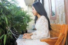 Asiatisches weibliches Mädchen oder Frau, welche die Laptops im Freien verwendet stockfotografie
