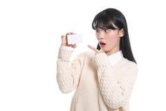 Asiatisches weibliches Studioporträt überraschte das Betrachten der Karte Stockbilder