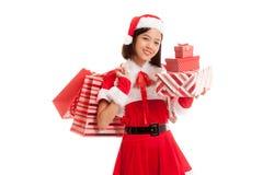 Asiatisches Weihnachts-Santa Claus-Mädchen mit Einkaufstaschen und Geschenk lizenzfreie stockfotos