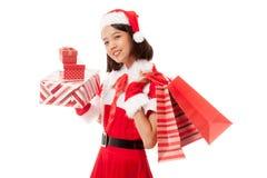 Asiatisches Weihnachts-Santa Claus-Mädchen mit Einkaufstaschen und Geschenk stockbilder