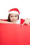 Asiatisches Weihnachtsmädchen mit Santa Claus kleidet Punkt unten zu blan stockfotografie