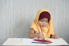 Asiatisches wenig Kleinkind/Baby tragendes hijab hat den Spaß, der lernt, Bleistifte zu benutzen Lizenzfreies Stockfoto