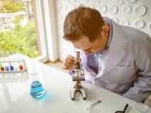 Asiatisches Wissenschaftlergebrauchsmikroskop stockfoto
