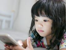 Asiatisches zu nah verwendendes und entlang eines Handys anstarrend Baby stockfotografie