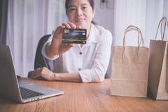Asiatisk äldre kvinnauppvisning som är falsk upp kreditkort, begrepp av shopping direktanslutet arkivfoto