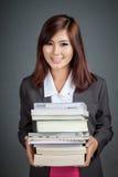 Asiatisk affärsflickahåll många böcker och leende Fotografering för Bildbyråer