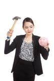 Asiatisk affärskvinna med den svinmyntbanken och hammaren Royaltyfri Foto