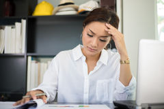 Asiatisk affärskvinna som är allvarlig om arbetet som göras till headacen royaltyfri bild