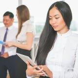 Asiatisk affärskvinna som använder minnestavlaPC tangentbordet och musen inramar insättningsblanketten och tjugo dollarräkningar Royaltyfri Fotografi