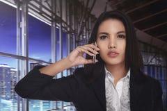 Asiatisk affärskvinna som kallar på telefonen som är sen på natten Arkivbild