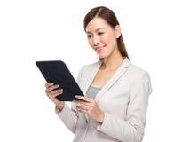 Asiatisk affärskvinna som läs på den digitala minnestavlan Arkivfoton