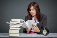 Asiatisk affärskvinna som läser många böcker royaltyfria foton