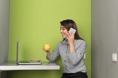 Asiatisk affärskvinna som talar på mobiltelefonappell genom att använda det bärbar datoraffärskvinnaIn Coworking Center kafét Royaltyfri Bild