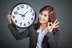 Asiatisk affärskvinnahåll ett reko tecken och leende för klockashow Arkivfoto