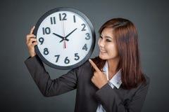 Asiatisk affärskvinnapunkt till en klocka och ett leende royaltyfri foto