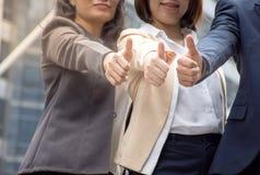Asiatisk affärslagtumme upp för bra arbete/framgång av teamwork royaltyfria bilder