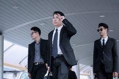 Asiatisk affärsman med gruppen av livvakten som går på affär s royaltyfri bild