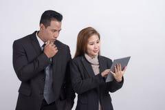 Asiatisk affärsman och affärskvinna som diskuterar idéer och använder den digitala minnestavlan på en vit bakgrund arkivfoton