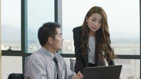 Asiatisk affärsman och affärskvinna som i regeringsställning arbetar lager videofilmer