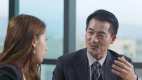 Asiatisk affärsman och affärskvinna som i regeringsställning diskuterar affär