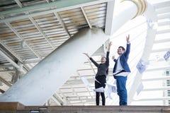 Asiatisk affärsman och affärskvinna som kastar papper i luften och upp lyfter två händer till berömd för lyckat i beskickning Royaltyfria Bilder