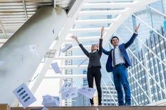 Asiatisk affärsman och affärskvinna som kastar papper i luften och upp lyfter två händer till gladlynt och berömd för lyckat Royaltyfri Foto
