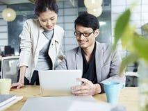 Asiatisk affärsman och kvinna som tillsammans i regeringsställning arbetar royaltyfria foton